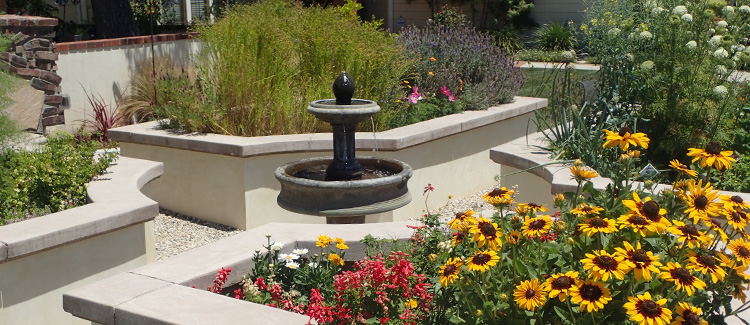 An image of a garden with a fountain and yellow sunflowers for Roger's Recommends