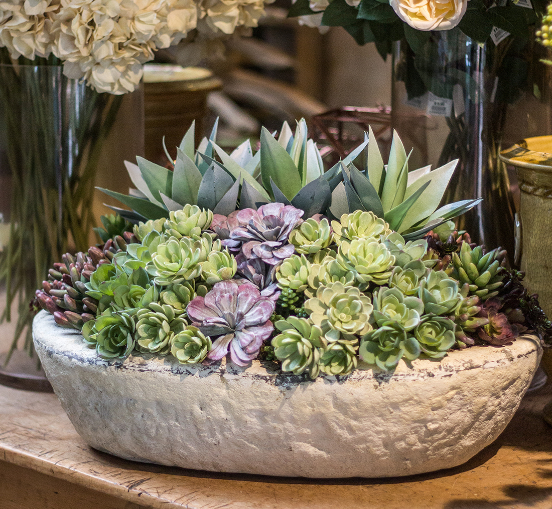 An image of a custom silk succulent in a stone bowl