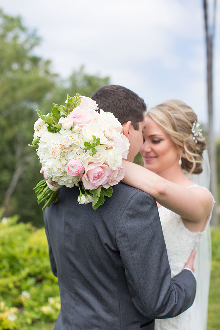 An image of the groom and bride who is holding a white and light pink rose bouquet from the Barlow Wedding