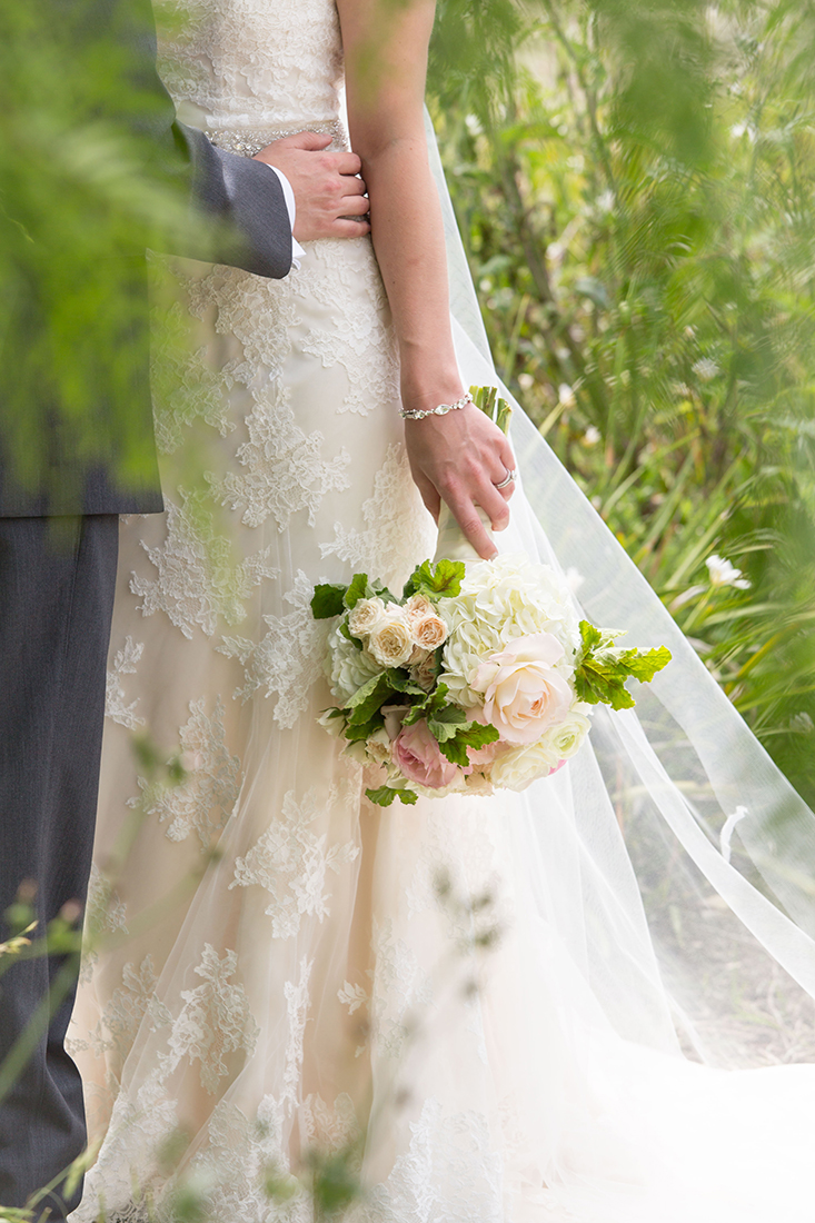 An image of the bride's arm holding the white and light pink rose bouquet