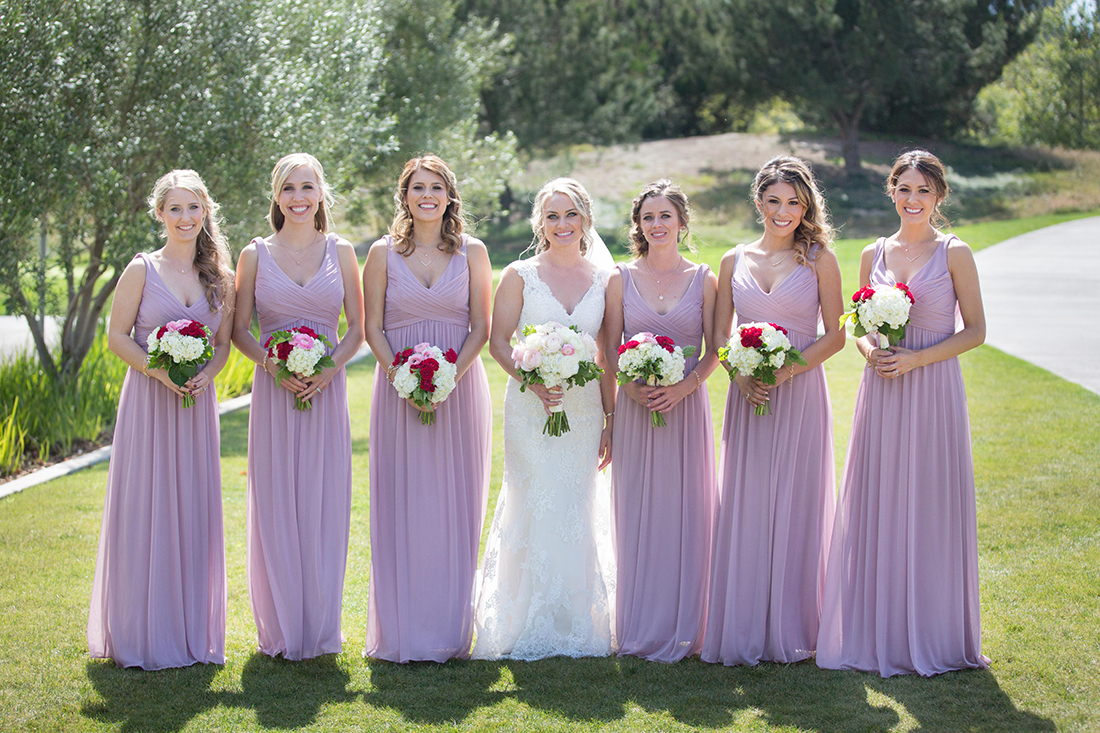 An image of the bridesmaids holding a white, red and light pink rose bouquet and the bride holding a white and light pink rose bouquet from the Barlow Wedding