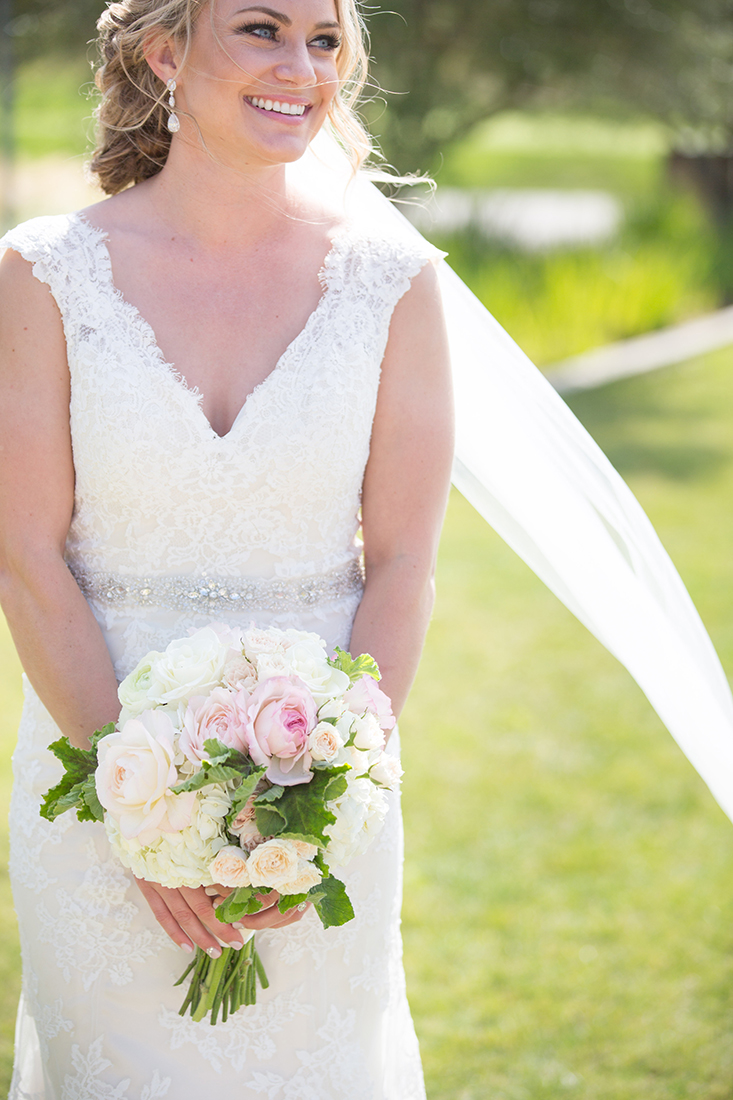 An image of the bride holding a white and light pink rose bouquet from the Barlow Wedding