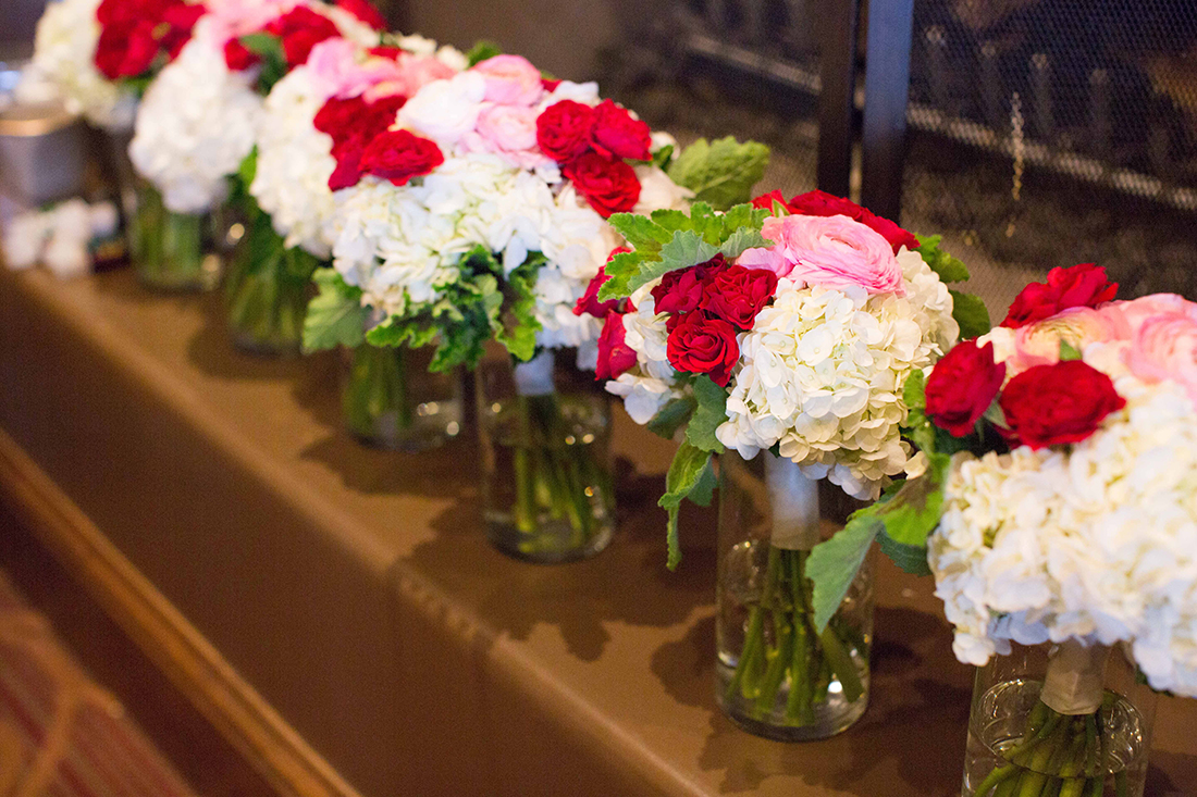 An image of red and pink roses with white hydrangea floral centerpieces for the Barlow Wedding