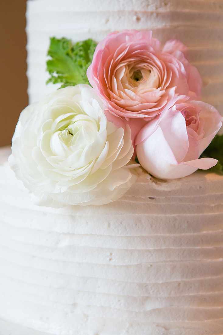 A close up image of the wedding cake with pink and white rose decoration for the Barlow Wedding
