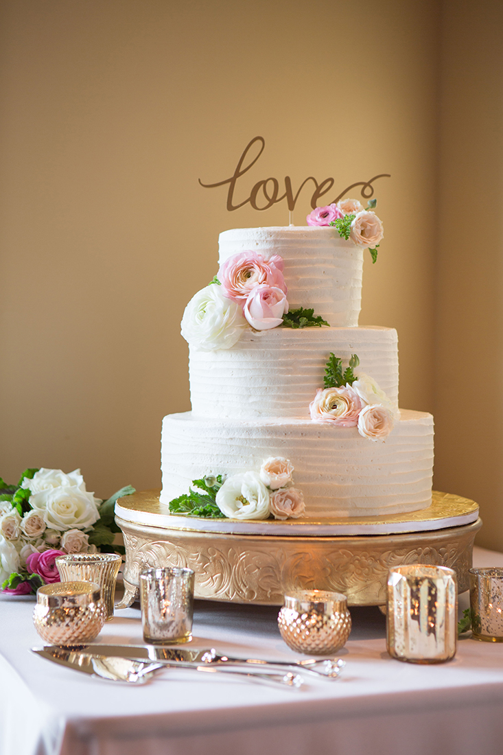 An image of the wedding cake decorated with white and light pink roses for the Barlow Wedding