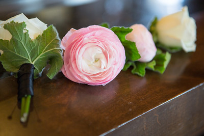An image of the white and light pink rose boutonnieres from the Barlow Wedding