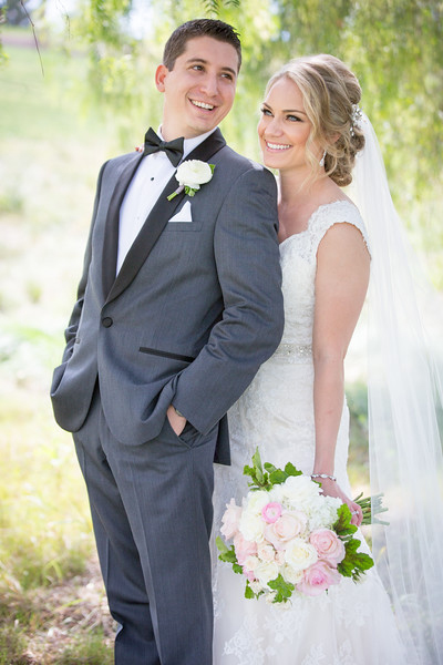 An image of the groom with a white rose boutonniereand bride with a white and light pink rose bouquet
