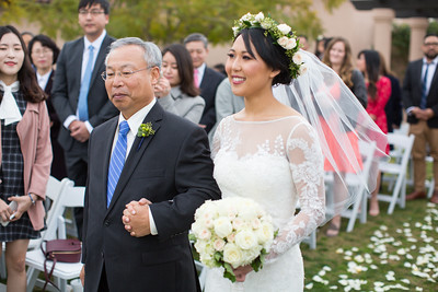 An image of the bride and her father walking down the aisle holding a white rose bouquet