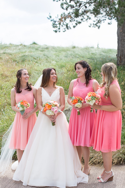 An image of the bride and bridesmaid holding white, light pink and orange rose bouquets from Cortez Wedding