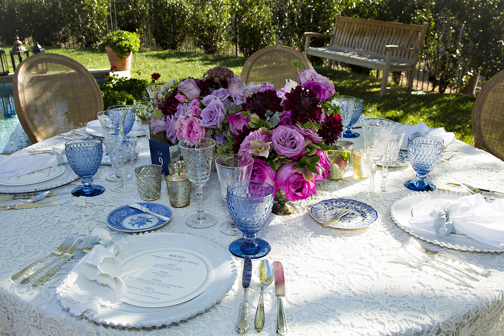 A close up image of a blue colored dining set up with magenta rose and dark red dahlias` floral center piece