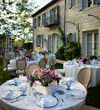 An image of a blue colored dining set up with magenta rose floral center piece