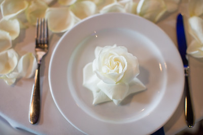 An image of a white rose placed on a white plate for dish setting at Lim wedding