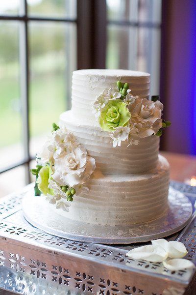 An image of a white wedding cake decorated with white and green flowers