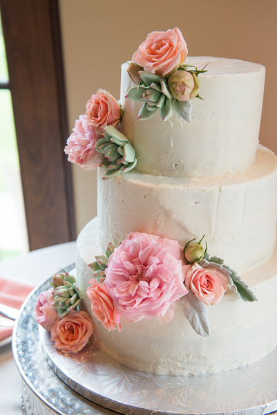 An image of the wedding cake with light pink rose decorations from the Cortez Wedding