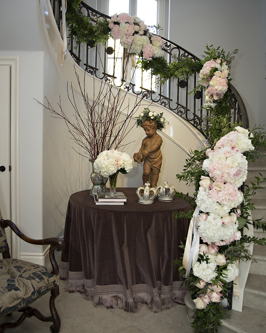 An image of a stairway railings decorated with light pink roses and white hydrangeas floral garland