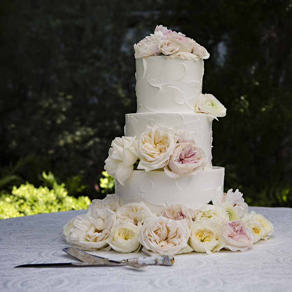 An image of the lovely white wedding cake decorated with white and light pink roses from the Dunzer Wedding