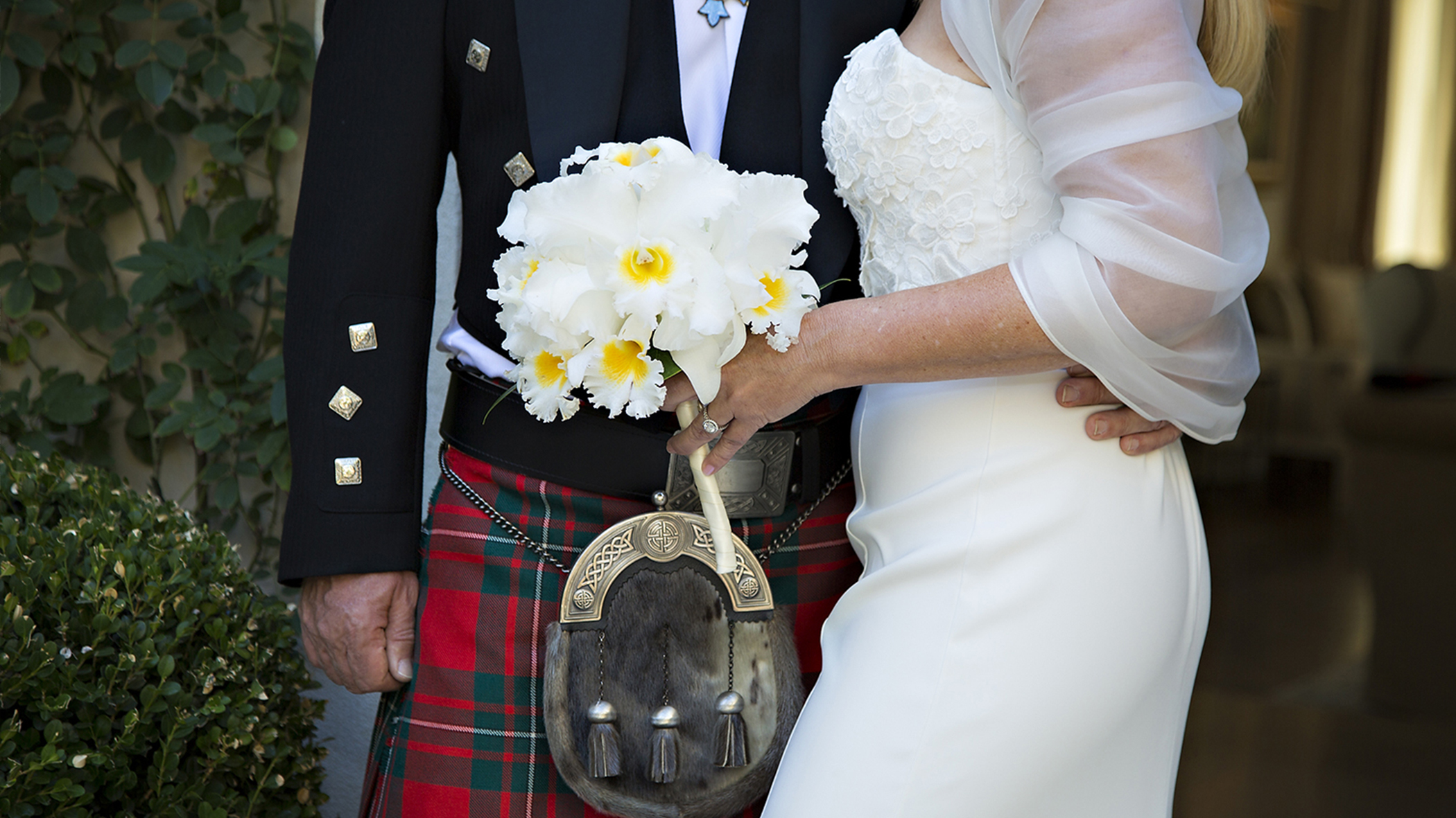 An image of a groom and bride who is holding a white flower bouquet