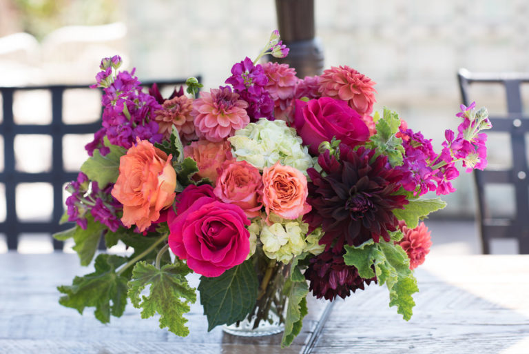 An image of a pink, orange, fuchsia and dark red flower floral arrangement