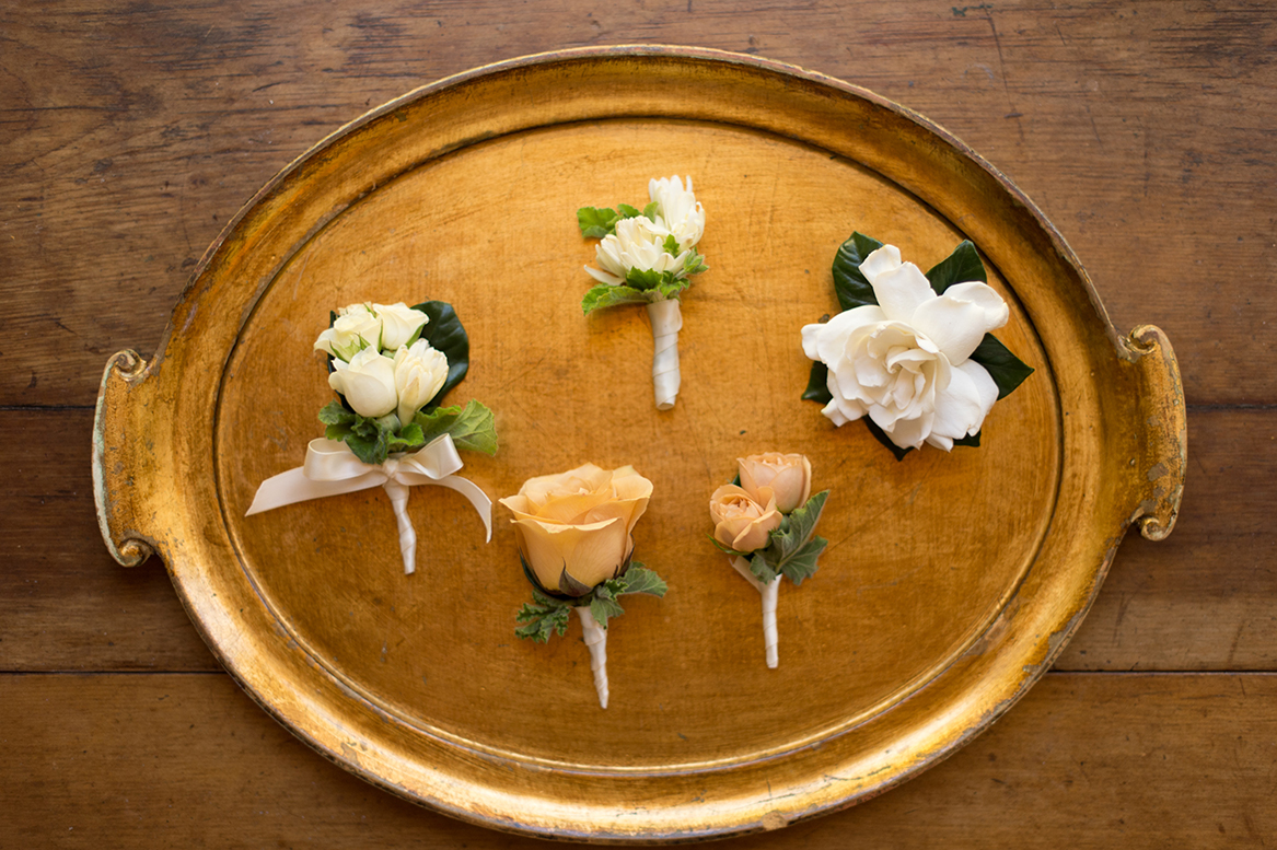 An image of the gardenia and rose boutonnieres on a gold tray