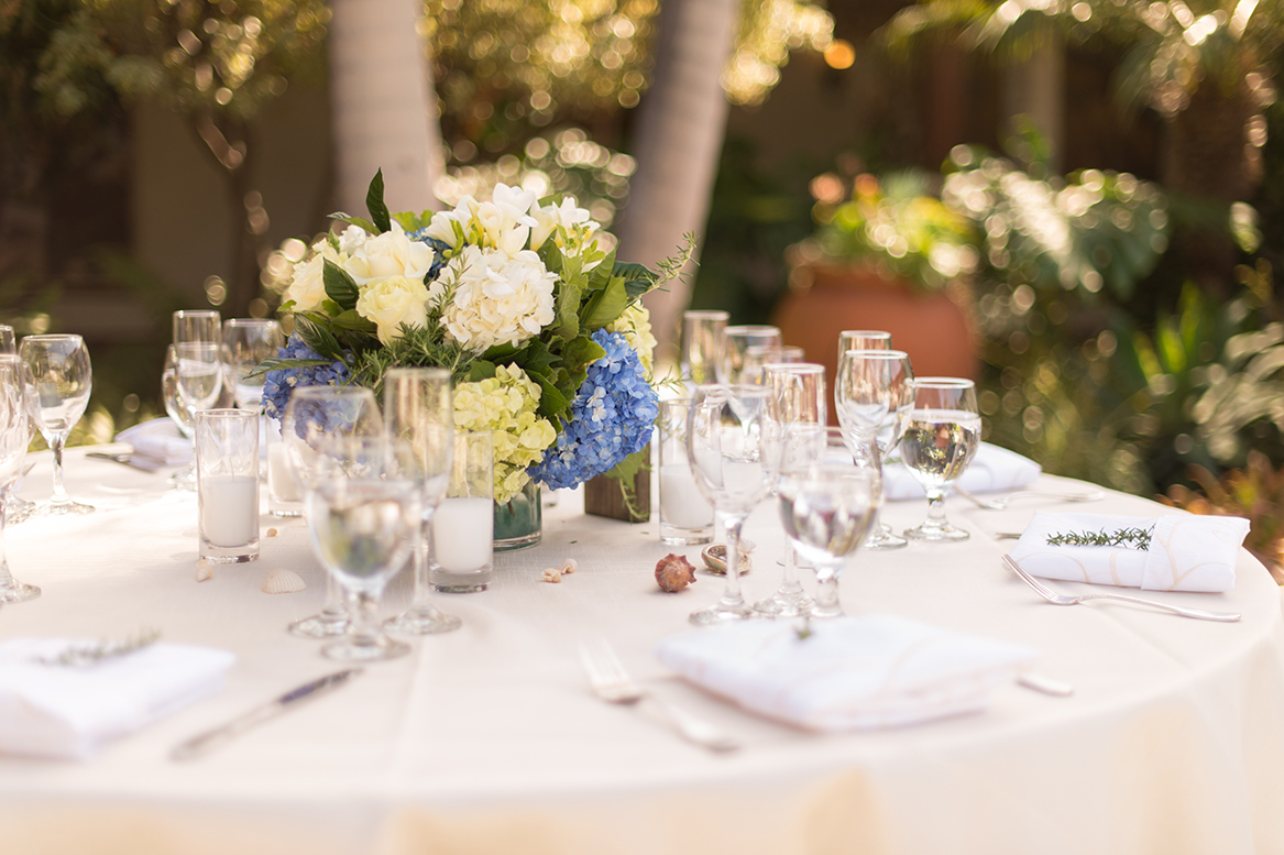An image of the table set up with a white and blue hydrangea centerpiece at the Premoli-Herbert Wedding