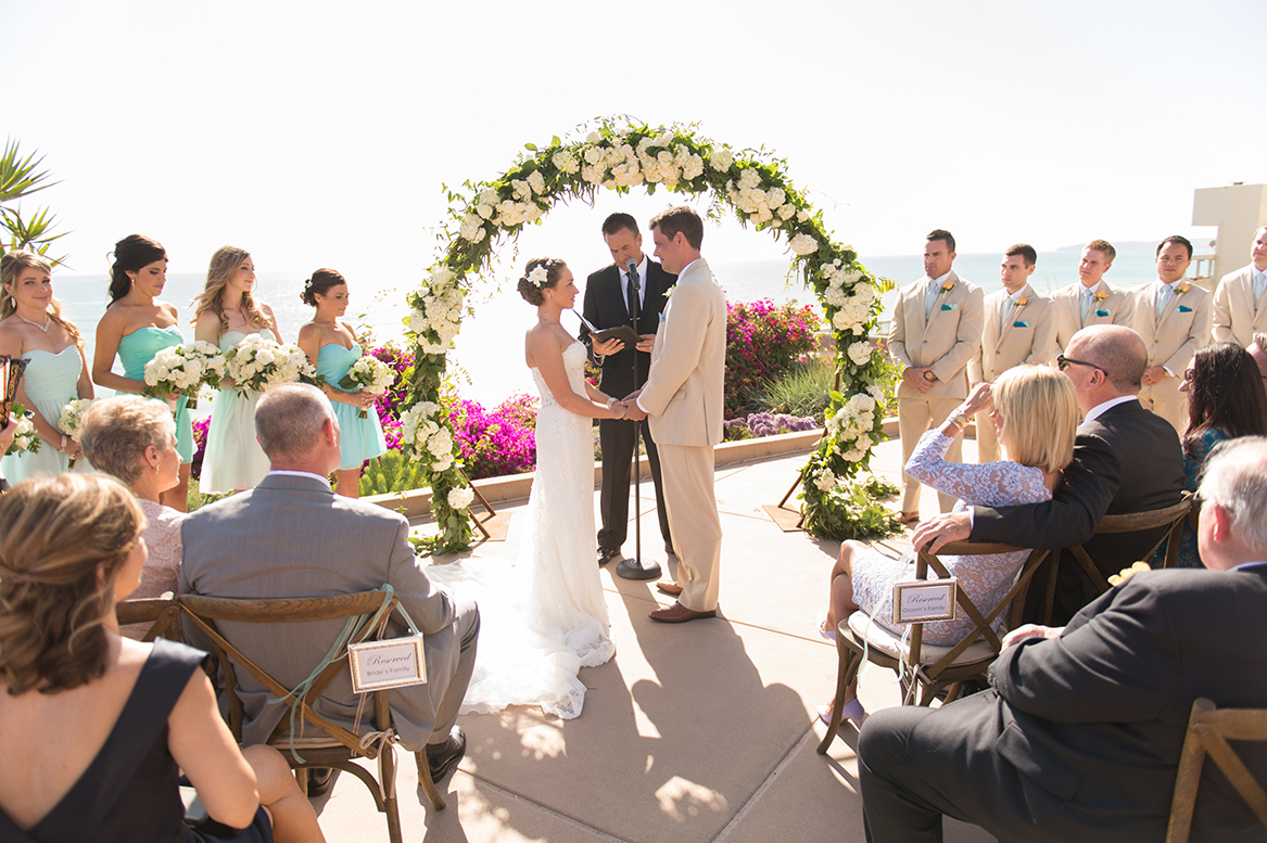 An image of the bride and groom at the alter with white rose and hydrangea arch decoration at the Premoli-Herbert Wedding