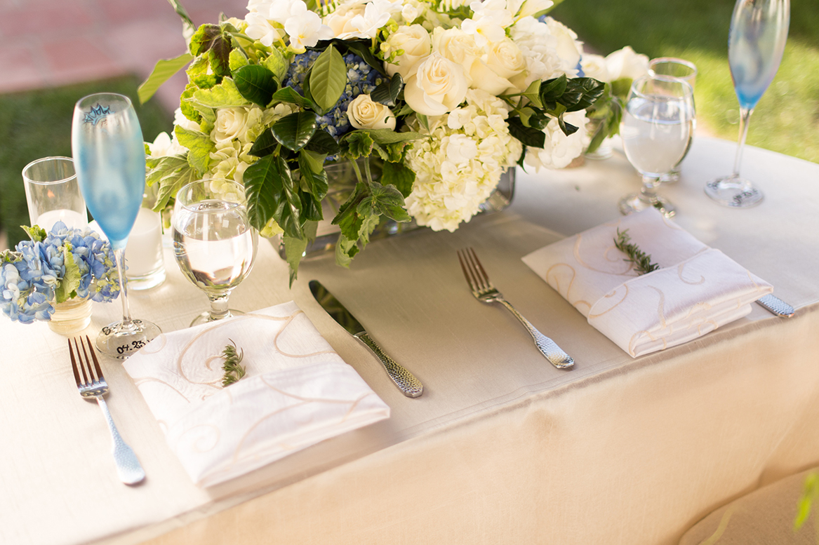 An image of the table display with a white rose and white and blue hydrangea centerpiece