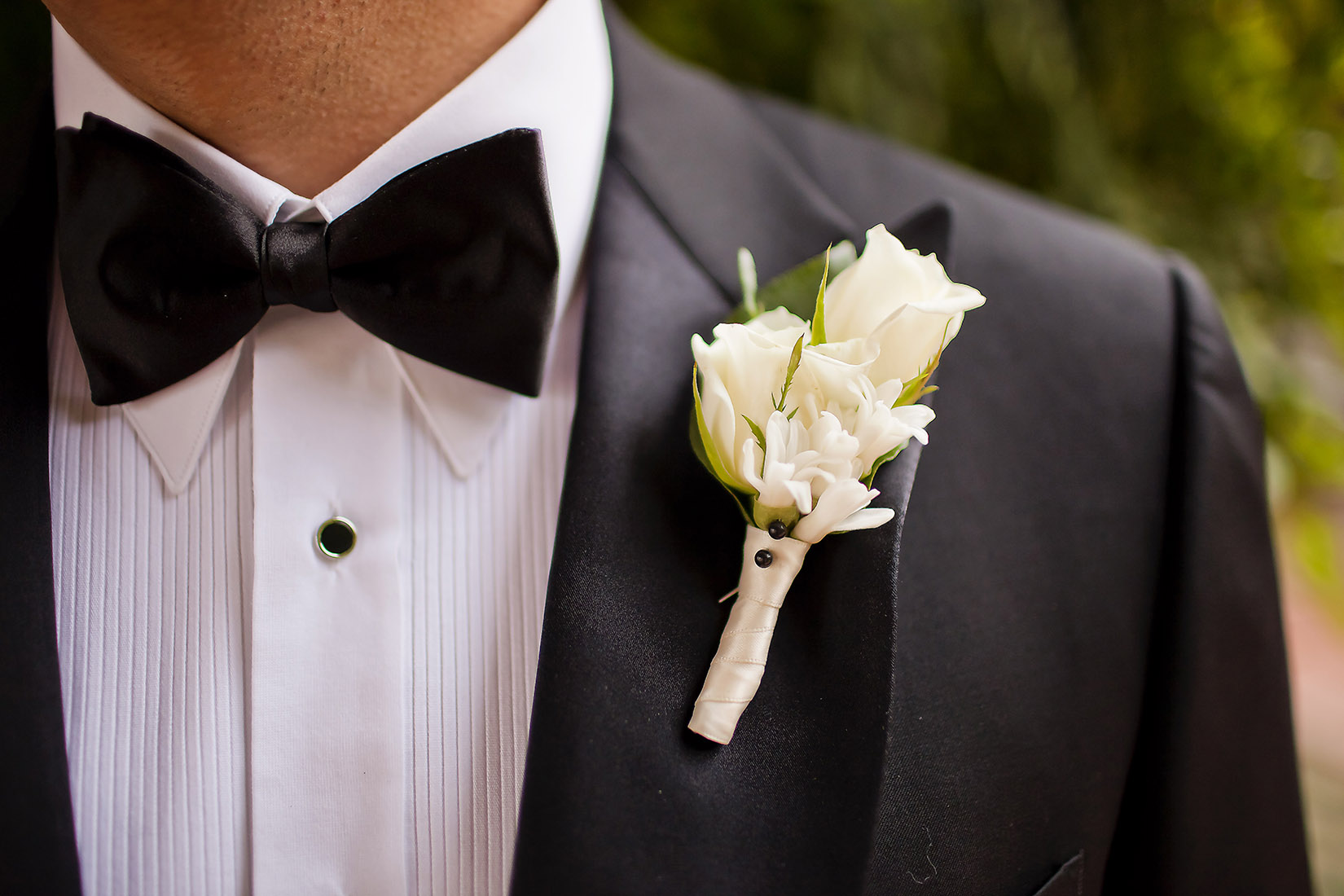 An image of a white rose boutonniere from the Lindsay & Shawn Wedding