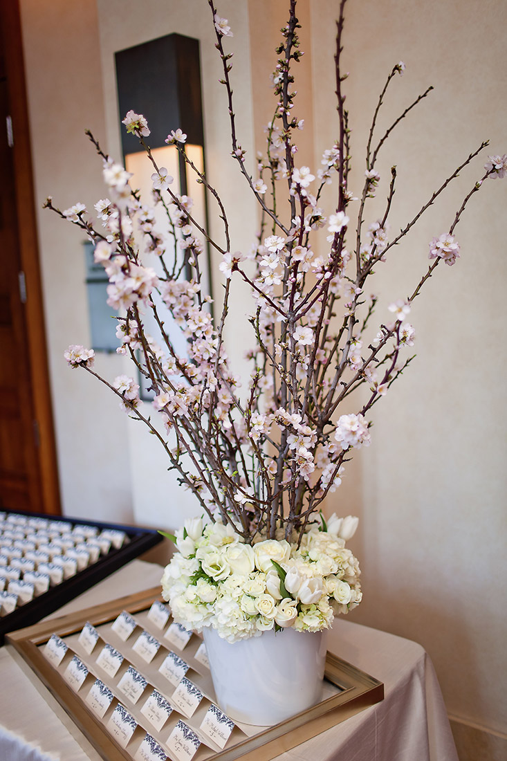 An image of pink cherry blossoms and a white rose and hydrangea floral arrangement from the Lindsay & Shawn Wedding