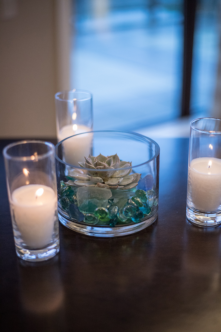 An image of three white candles in skinny glass holders surrounding a glass dish with a succulent planted in tiny blue and green glass pebbles