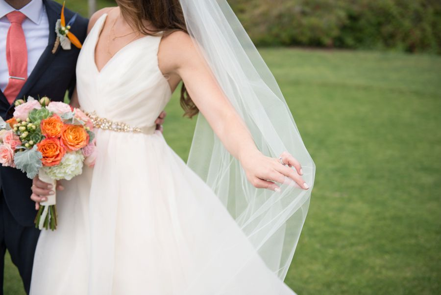 An image of the bride holding a orange, white and light pink rose bouquet from the Cortez Wedding