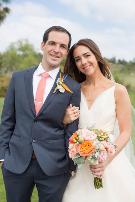 An image of Mr. and Mrs. Cortez who is holding a pink and orange flower bouquet