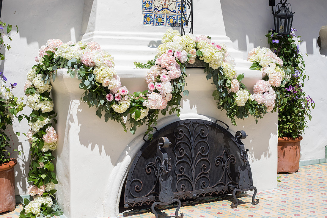 An image of a fireplace decorated with light pink rose and white hydrangea garland
