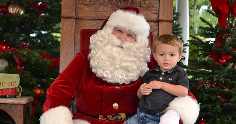 An image of a child posing with Santa