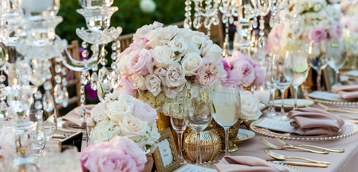 An image of a wedding dining set up with a white and light pink rose floral centerpiece