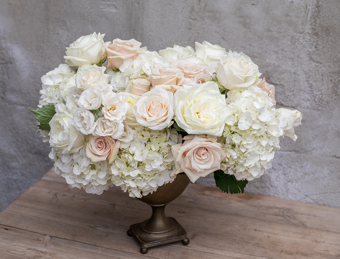 An image of white and light orange roses as well as white hydrangeas for a floral wedding arrangemetn