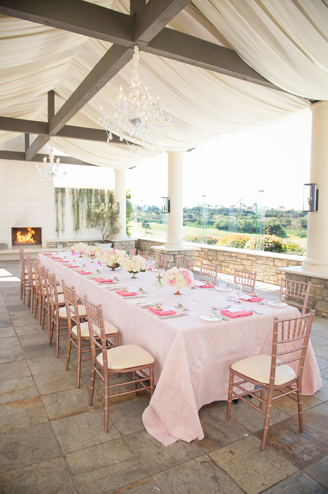 An image of a pastel pink dining set up with pink and white rose floral centerpieces