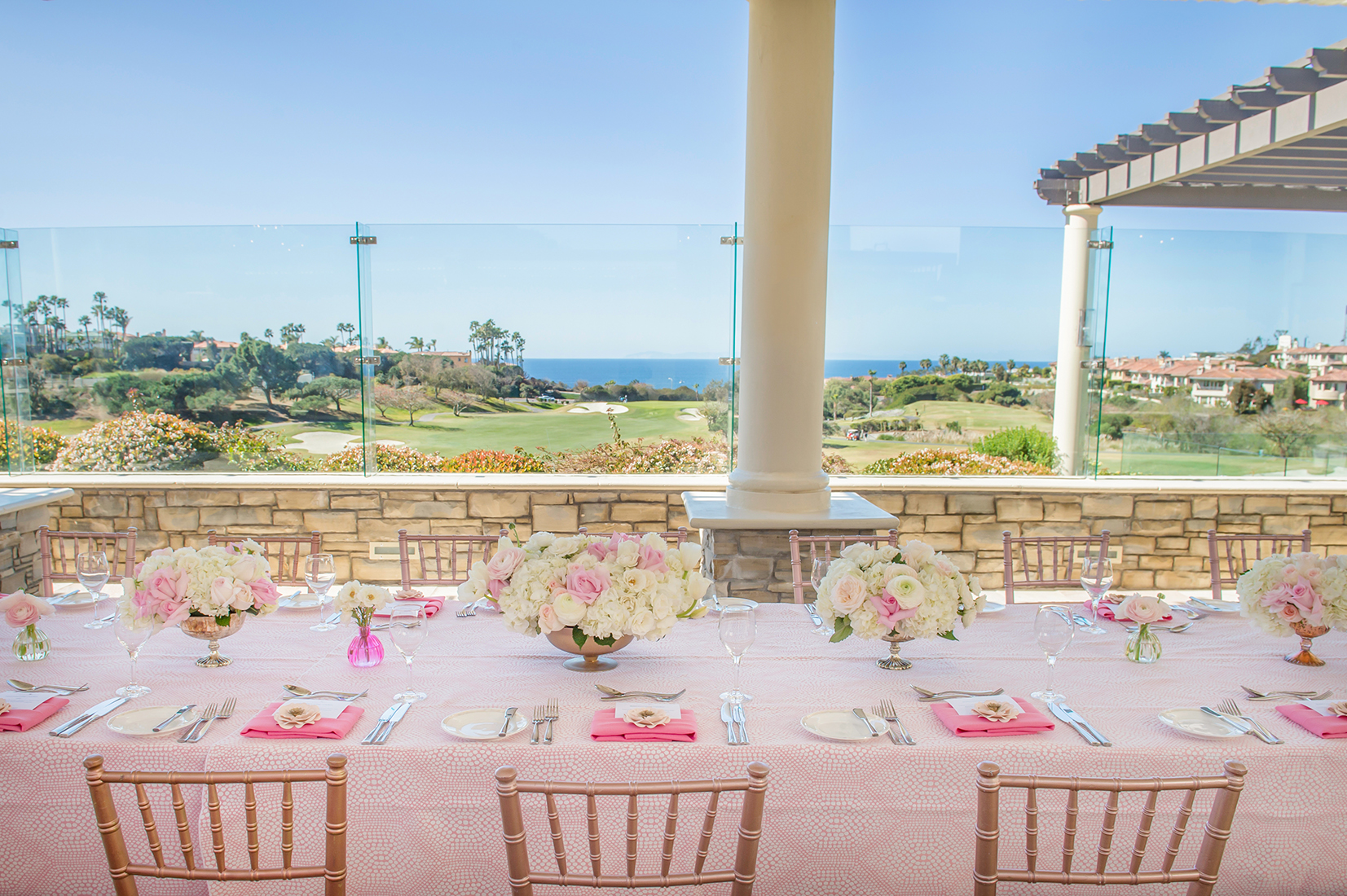 A close up image of the pastel pink dining set up with white and pink rose floral center pieces
