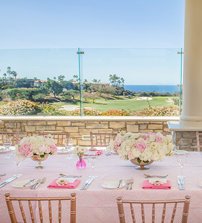 An image of a pastel pink dining set up with white and pink floral center pieces