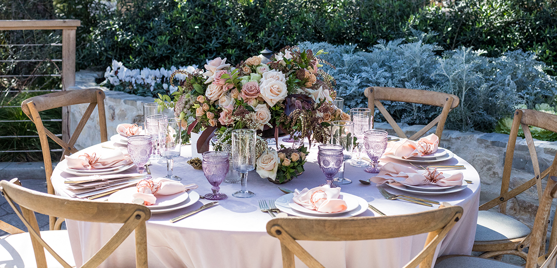 An image of pastel colored dining set table with a pastel rose colored floral arrangement