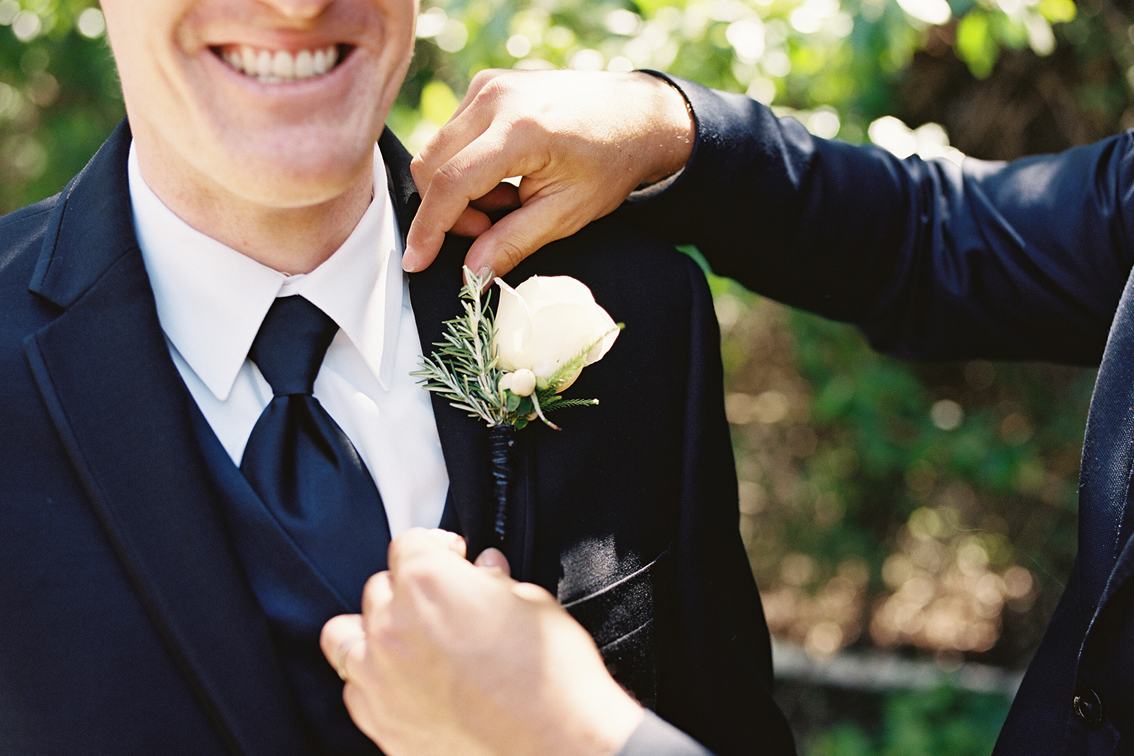 An image of a groom smiling as one of his friends attaches a white rose boutonniere to his suit