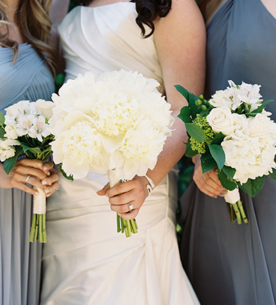 An image of a bride and two bridesmaids featuring white flowered bouquets