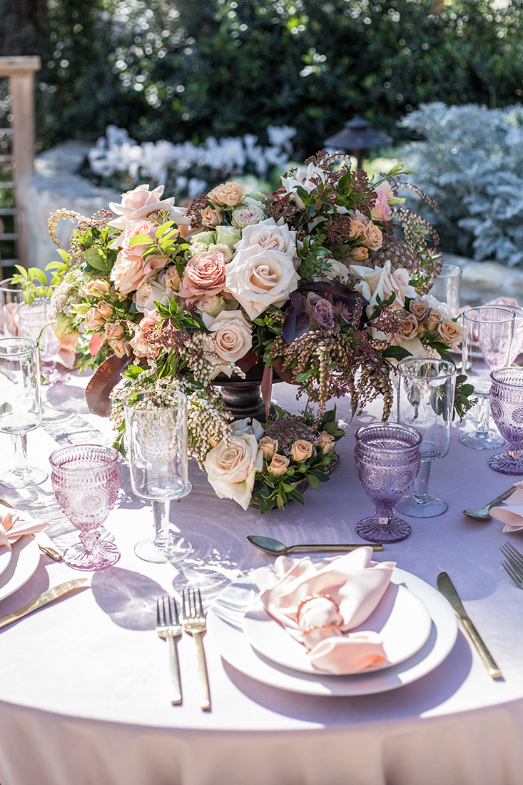 A close up image of pastel colored dining set table with a pastel rose colored floral arrangement