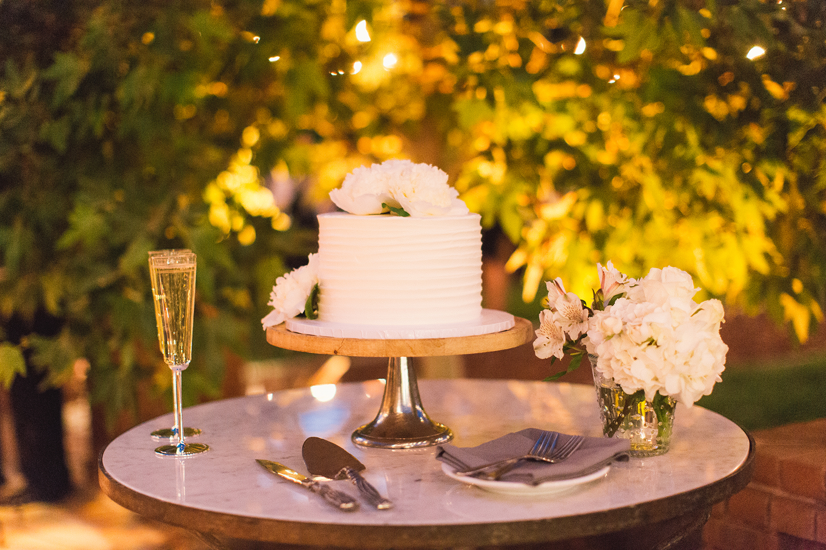 An image of the wedding cake top with white roses, glasses of champagne, and a white hydrangea floral arrangement