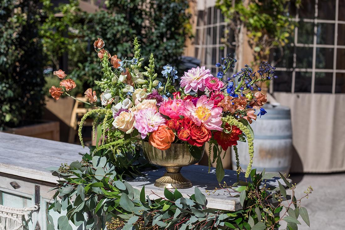 An image of a orange, pink and light blue flowered boho floral arrangement