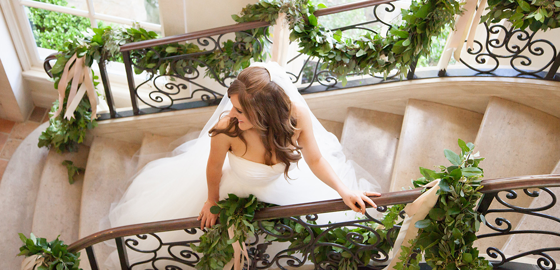 An image of a bride walking up a stone stairway with green wedding garland looped through the railings