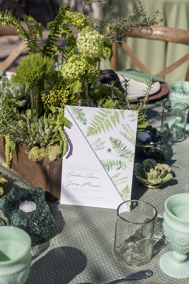 An image of the wedding invitation for the Forged Greenery decorated with green hydrangea and succulent arrangement