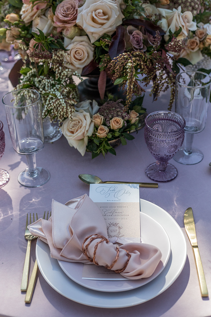 An image of the pastel colored dining set up with the invitation displayed underneath a pink napkin with a transparent lavender glass and gold silverware