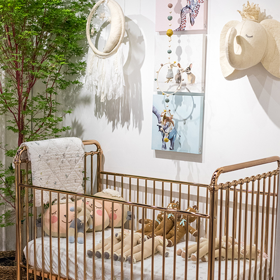 An image of a metal copper crib with various plush animals in it with a mobile above it with wall decorations in the children's gift boutique