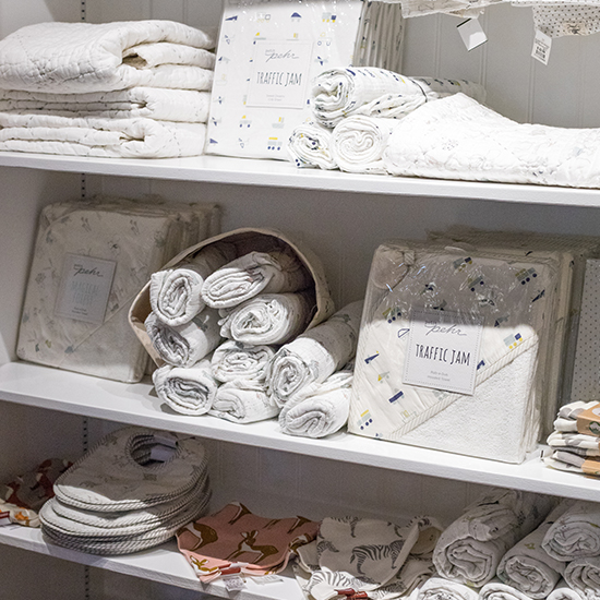 An image of white themed baby sheets in the baby room at Roger's Gardens