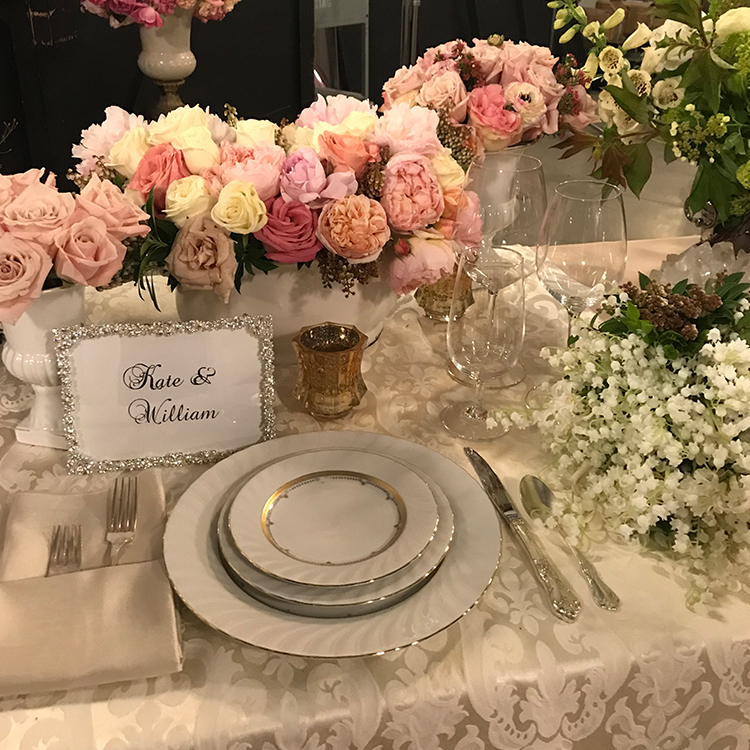 An image of the table set up with gold trim dishes and a white and pink rose floral